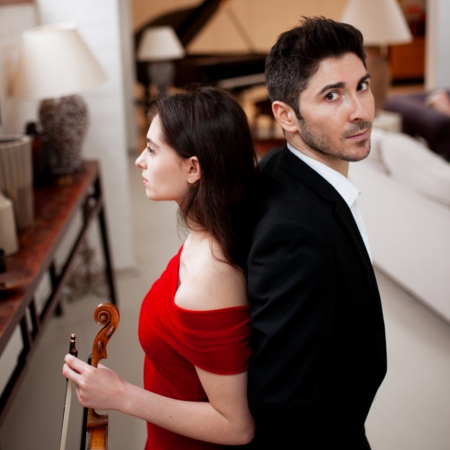 Esther Abrami and Niccolo Ronchi stand back to back. She holds her violin and the piano looms ominously in the background.